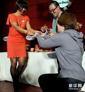 Professional tennis champion Li Na presents an autographed photo to a fan during a publicity event held by a sponsor, ice cream maker Haagen-Dazs, in 2011 in China.