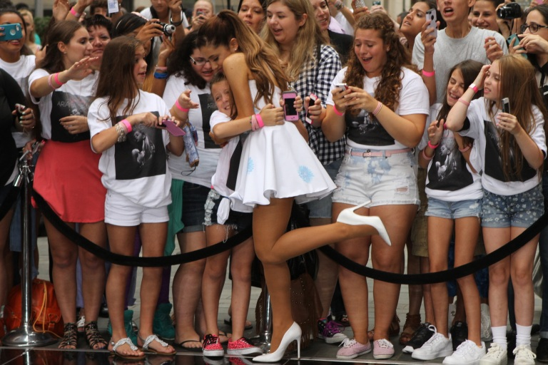 Ariana Grande, always wearing sheer suntan pantyhose and high heels, greets young adoring fans before performing a concert recently in New York City.