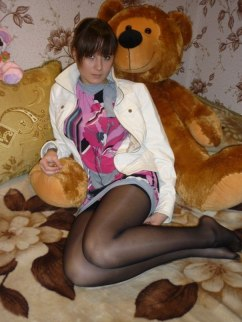 Unidentified young lady in pantyhose lounges with her bear